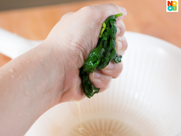 Squeezing the excess liquid from blanched spinach